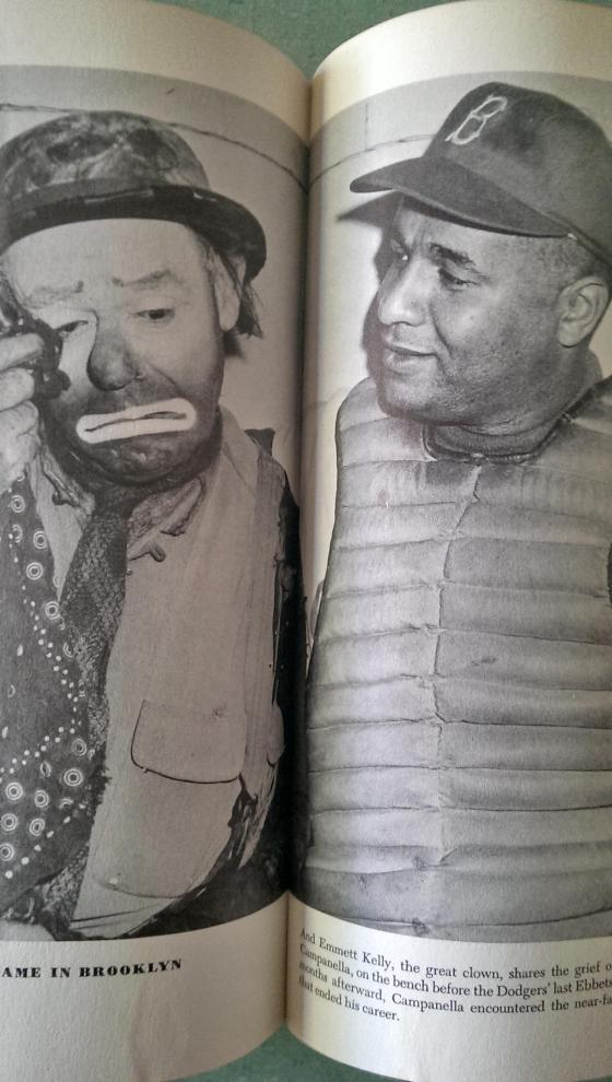 """Emmett Kelly, the great clown, shares the grief of the moment with Roy Campanella, on the bench before the Dodgers' last Ebbets Field appearance.  Short months afterward, Campanella encountered the near-fatal automobile accident that ended his career""."